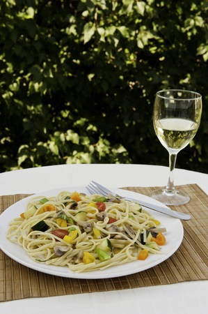Plate of colorful vegetable linguini with a glass of white wine photo