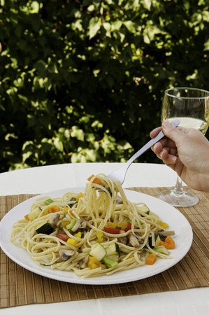 Fork full of colorful vegetable linguini to be enjoyed outdoors in the summer photo