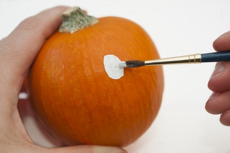 decorating: Hands decorating a pumpkin with paint Stock Photo