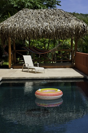 A lounge chair overlooks a colorful tube floating in a pool with a hammock in the background Stock Photo
