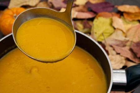 鍋からバター スカッシュのスープをすくい取鍋 写真素材