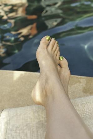 女性の足は、プールサイドのラウンジチェアでリラックスします。 写真素材