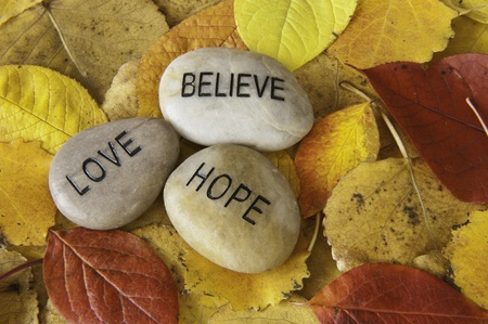 hope: Believe, love and hope message rocks with colorful fall leaves Stock Photo