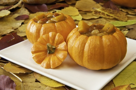 Pumpkin soup in mini pumpkin bowls with colorful fall leaves