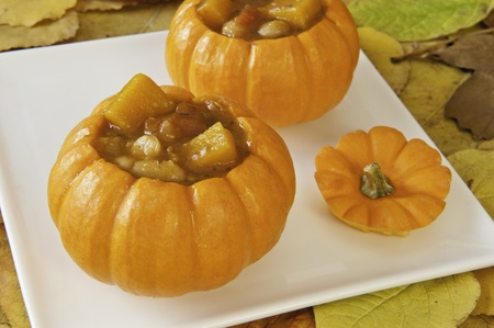 Mini Pumpkins filled with pumpkin soup surrounded by fall leaves