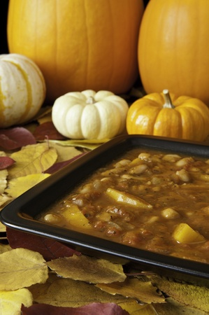 Hearty pumpkin stew in a black dish with autumn leaves and pumpkins Stock Photo