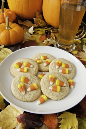 Plate of candy corn cookies and cup of tea with colorful fall leaves and pumpkins photo