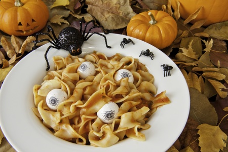 Dish of noodle brains and eyeballs with halloween spiders and a jock-o-lantern photo