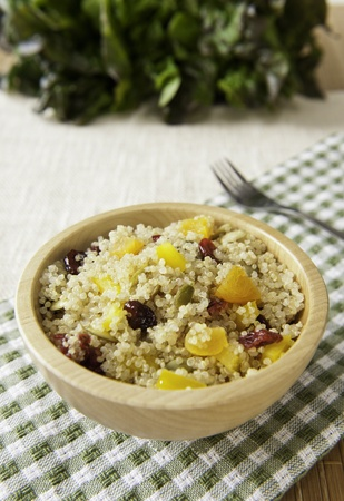 Bowl of healthy quinoa salad with dried fruit and pumpkin seeds