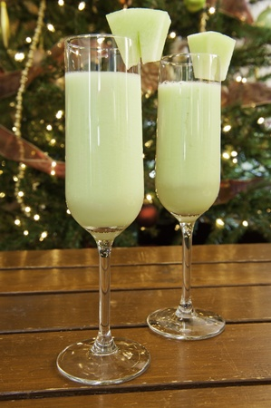 two fluted glasses of honeydew Melon smoothies with Christmas tree