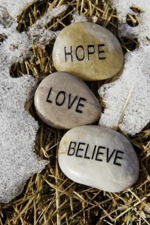 Hope, Love and believe rocks in the melting spring snow