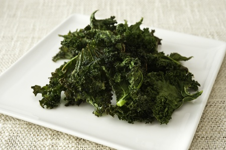 snack: Healthy snack of a plate of roasted kale chips Stock Photo