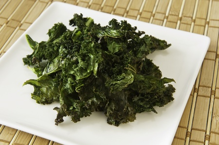 kale: Nutritious snack of roasted kale chips on a white plate