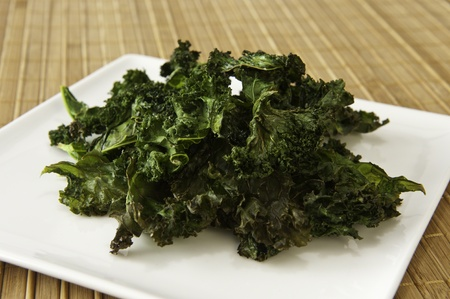Plate of roasted kale chips on a bamboo matt