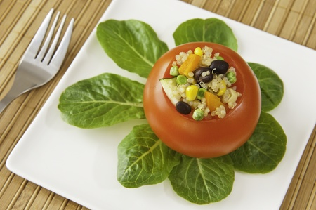Tomato stuffed with quinoa, black beans and vegetables with greens on a white plate photo