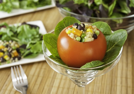 Appetizing tomato stuffed with quinoa salad and greens photo