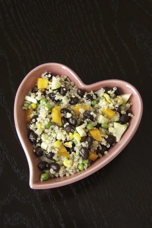 Heart-shaped dish of quinoa salad on a dark wood table Stock Photo