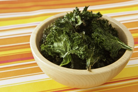 Wooden dish of roasted kale chips on a colorful table cloth