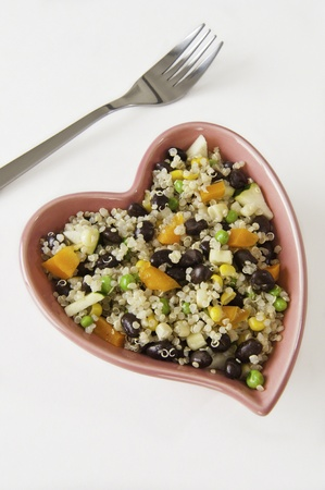 Heart shaped dish filled with quinoa and vegetable salad photo