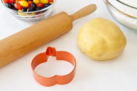 cutter: Cookie dough, pumpkin shaped cookie cutter, rolling pin and jellybean Stock Photo