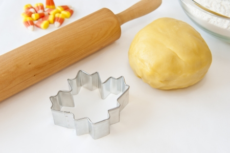 cutter: Cookie dough, Maple leaf shaped cookie cutter, rolling pin and candy corn Stock Photo