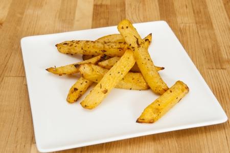 rutabaga: White plate of rutabaga fries on wood