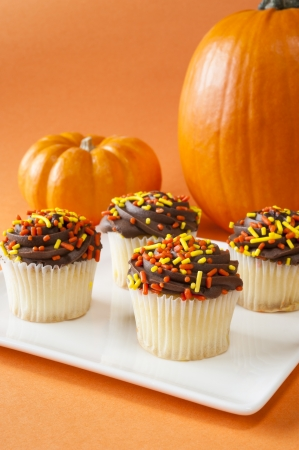 White cupcakes with chocolate icing and sprinkles with pumpkins Stock Photo