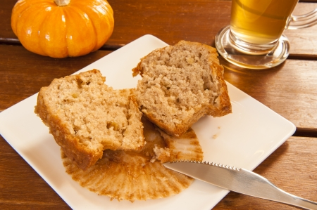 Muffin sliced in half on a plate with a cup of tea and a pumpkin