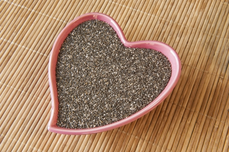 Pink heart shaped dish of chia seeds Stock Photo