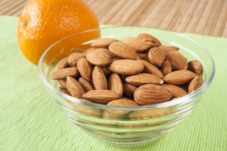 Dish of fresh raw almonds with an orange