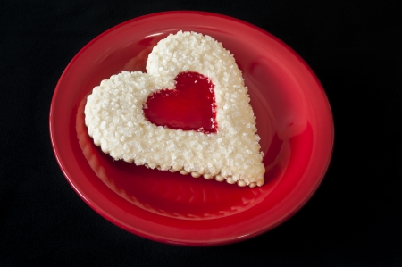 Heart shaped sugar cookie with a strawberry jam heart shaped center photo