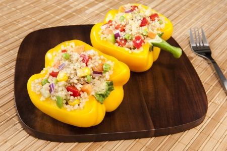 Two yellow peppers stuffed with quinoa and mixed vegetables