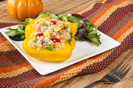 the greens: Yellow pepper stuffed with quinoa salad on a white plate with mixed greens Stock Photo