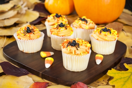 Halloween cupcakes with candy corns, pumpkins and fall leaves photo