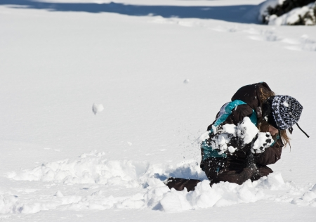 Girl ducks to avoid a snowball in a snowball fight