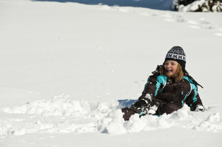snow break: Girl laying in the snow while taking a break from playing