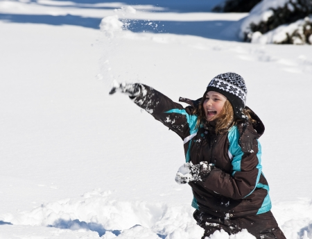Girl throwing a snowball on a sunny winter day