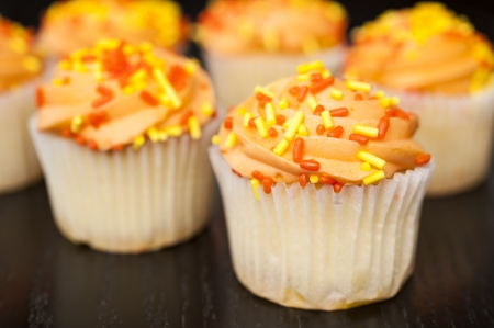 Cupcake with orange icing and yellow and orange sprinkles photo