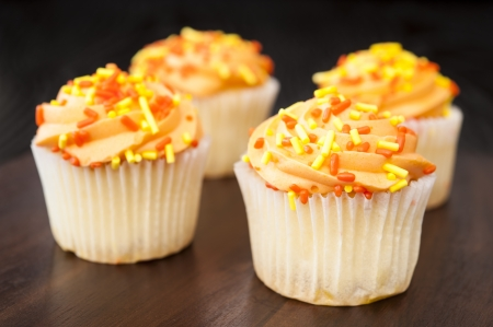 Four white cupcakes with orange icing and yellow and orange sprinkles photo