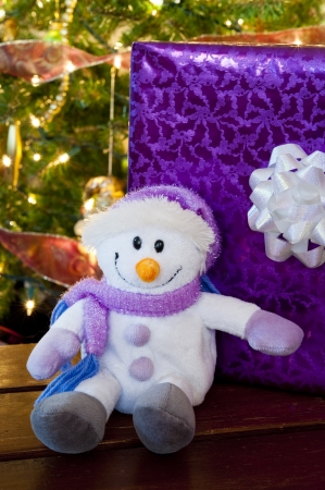 Smiling stuffed snowman with a purple present and a Christmas tree Stock Photo
