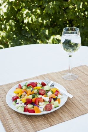 garbanzo bean: Fresh chickpea and vegetable salad with a glass of water served outdoors