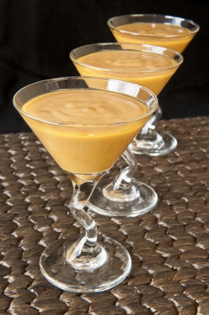 carmel: Martini glass of carmel pudding on a woven mat Stock Photo