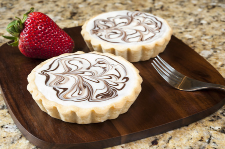 Two white chocolate tarts on a granite background Stock Photo
