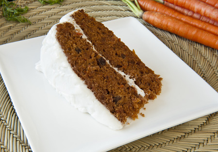 Slice of carrot cake with white frosting on a white plate