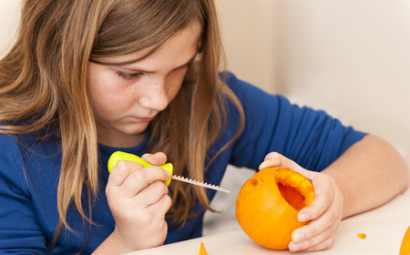 decorating: Girl focuses while carving a pumpkin for Halloween
