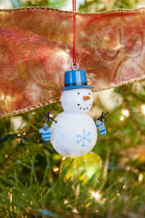 Snowman decoration hanging on a Christmas tree