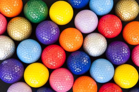 putt: Assortment of colorful mini golf balls on black