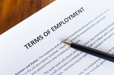 Contract outlining the terms of employment with a pen