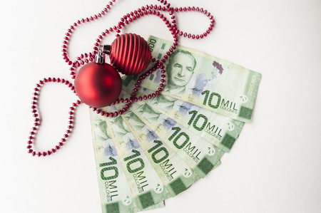 Christmas bonus of Costa Rican colones and red Christmas decorations Stock Photo