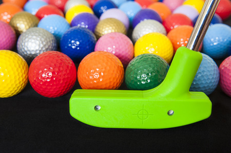 Colorful mini golf balls with a green club Stock Photo